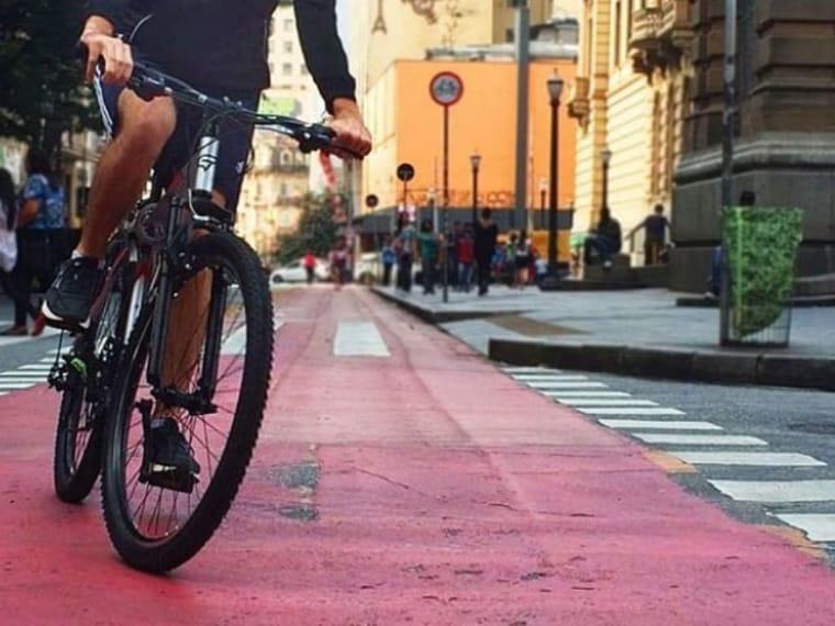 #pracegover imagem de uma bicicleta em uma ciclovia de piso vermelho em frente ao teatro municipal no centro de São paulo